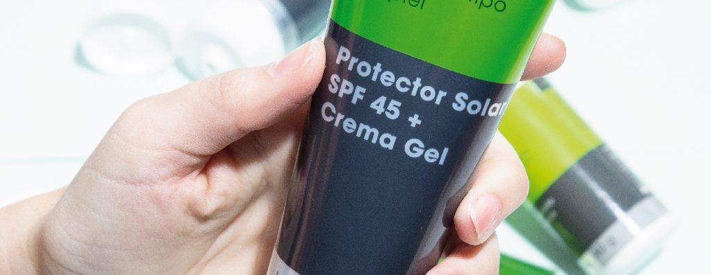 Mano sosteniendo recipiente de protector solar SPF 45+ Crema Gel